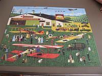 "This mosaic puzzle is made out of wooden tiles. Titled ""Four Aces Flying School""."